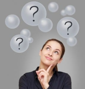 Thinking business woman looking up on many bubbles with question