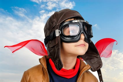Young boy pilot against a blue cloudy sky