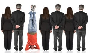 business people backwards with a casual guy doing the headstand