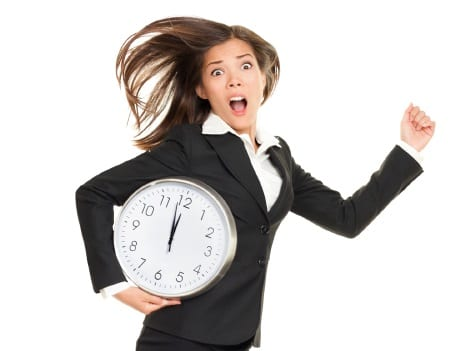 Stress - business woman running late with clock under her arm. Business concept photo with young businesswoman in a hurry running against time. Caucasian / Chinese Asian isolated on white background in full length.